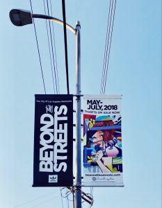 A photo showing a BEYOND THE STREETS banner hanging on a streetlight pole